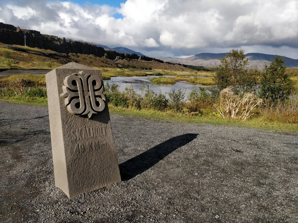 "A stone waymarker reading ""Skalholt 49 KM"" in Thingvellir National Park, Iceland."
